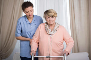 Aged disabled lady with walker and her helpful caregiver