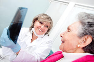 Dentist with an elder female patient looking at an x-ray-1