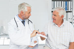 Male doctor giving a prescription to his senior patient at the medical office