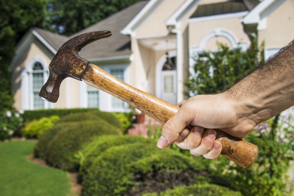 Mans hand holding hammer in front of a house indicating home improvement and maintenance.-1