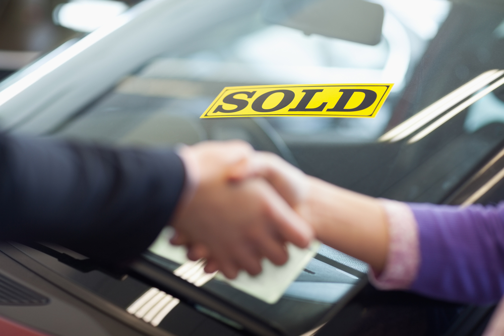 People shaking hands in front of a sold car-1