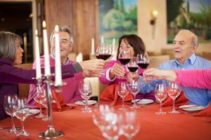 People toasting wine glasses at restaurant table