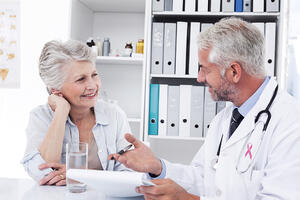 Pink awareness ribbon against female senior patient visiting a doctor