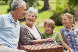 Portrait of a smiling senior couple and grandchildren at the park-1