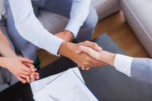 home inspector shaking hands with client with contract on the coffee table