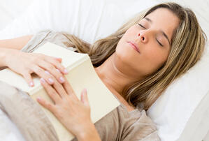 Beautiful woman falling asleep while reading a book