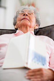 Elder woman falling asleep upright while reading a book