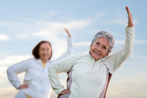Elder women in a stretching class outdoors fitness concepts