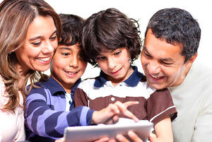 Family holding a tablet computer and looking at it