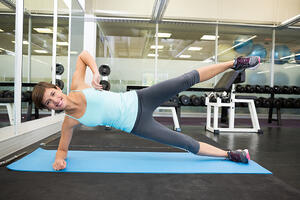 Fit smiling brunette doing pilates on exercise mat at the gym