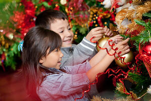 Happy kids decorating a Christmas tree with balls