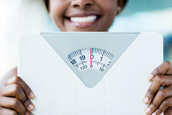Happy woman holding a weight scale at the gym