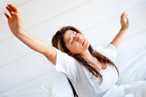 Lazy woman in bed waking up and yawning