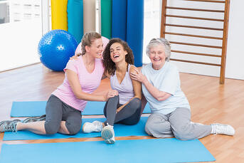 Playful female friends sitting together on exercise mat in gym