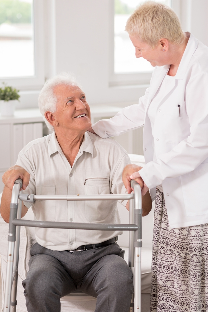 Professional carer helping her elderly patient to use a walking frame