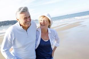Senior couple walking on the beach in fall season-1