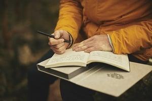 older woman writing in gratitude journal outside