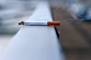 smoldering cigarette left on railing