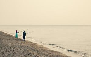 older couple fishing together on the beach