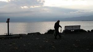 senior man walking alone in park with depression