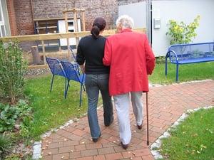 caretaker helping older woman walk through park