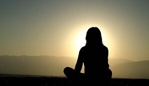 practicing meditation at sunset