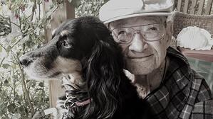older man smiling holding therapy dog