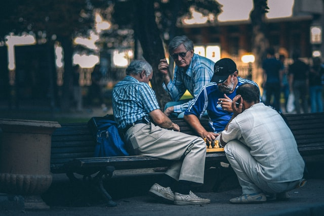 group of men friends playing chess in the park