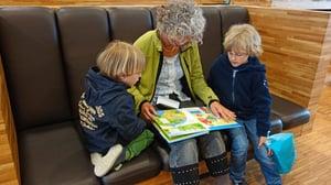 grandmother reading to twin grandchildren