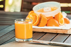 fresh squeezed orange juice with squeezed orange peels in background