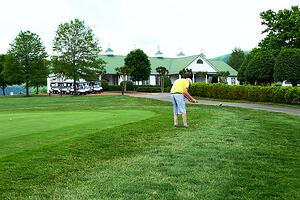 senior man golfing chipping off the green