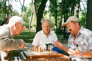 Three older men playing chess together outside in a park