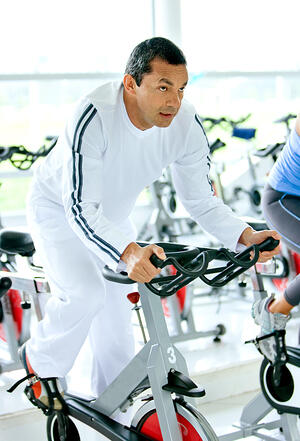 man at the gym doing cardio exercise on spin bike