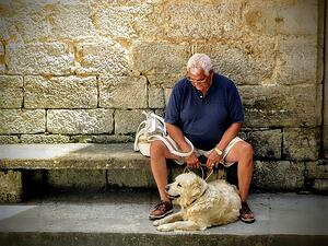 older man outdoors with pet dog