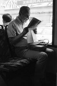 man reading newspaper on bus