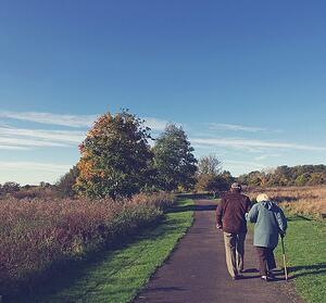 senior couple walking on path outdoors