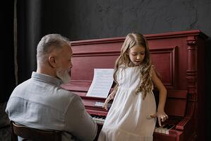 grandfather playing piano with granddaughter