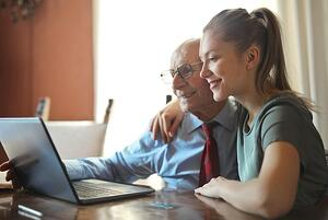 older man and daughter researching communities together online
