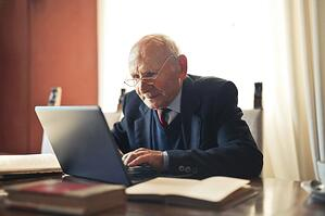 older man leaning over to see computer at desk