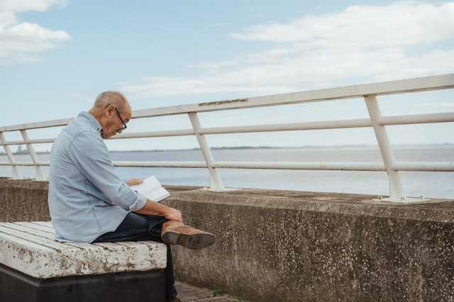 older man alone reading on a pier