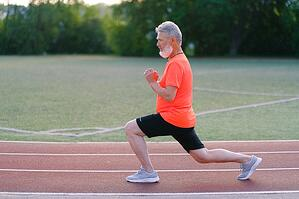 older man performing calishtenic exercise on a track outdoors