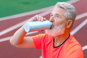 older man hydrating with water bottle on outdoor track