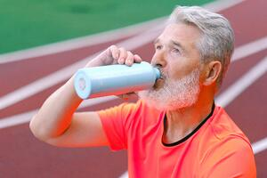 man drinking water at track