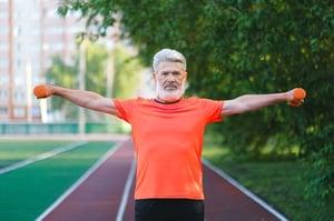 senior man lifting weights outdoors