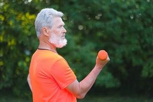 older man exercising biceps outdoors