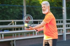 older gentleman playing tennis outdoors
