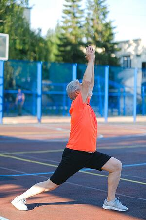 Older man stretching outdoors on a track