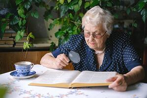 Retired woman reading at dining table