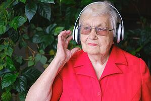 older woman listening to music with over the ear headphones