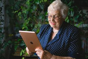 older woman reading blog posts on her ipad tablet